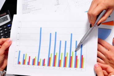 Teamwork in office with two unrecognizable businesswomen with financial charts