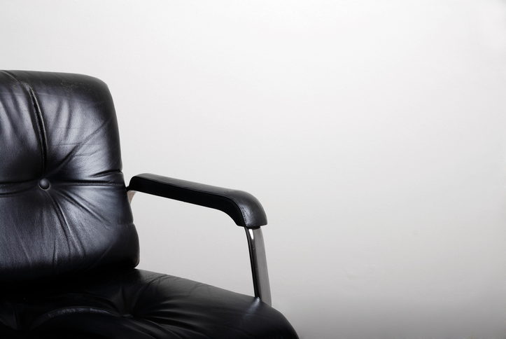 Empty black directors chair and a white wall