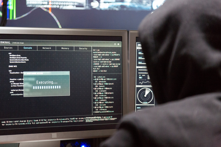 Back View of Teenage Hacker Working in Computer and Infecting with Virus Data Servers of Government Infrastructures.