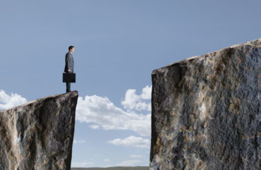 Businessman Standing At Edge Of Cliff