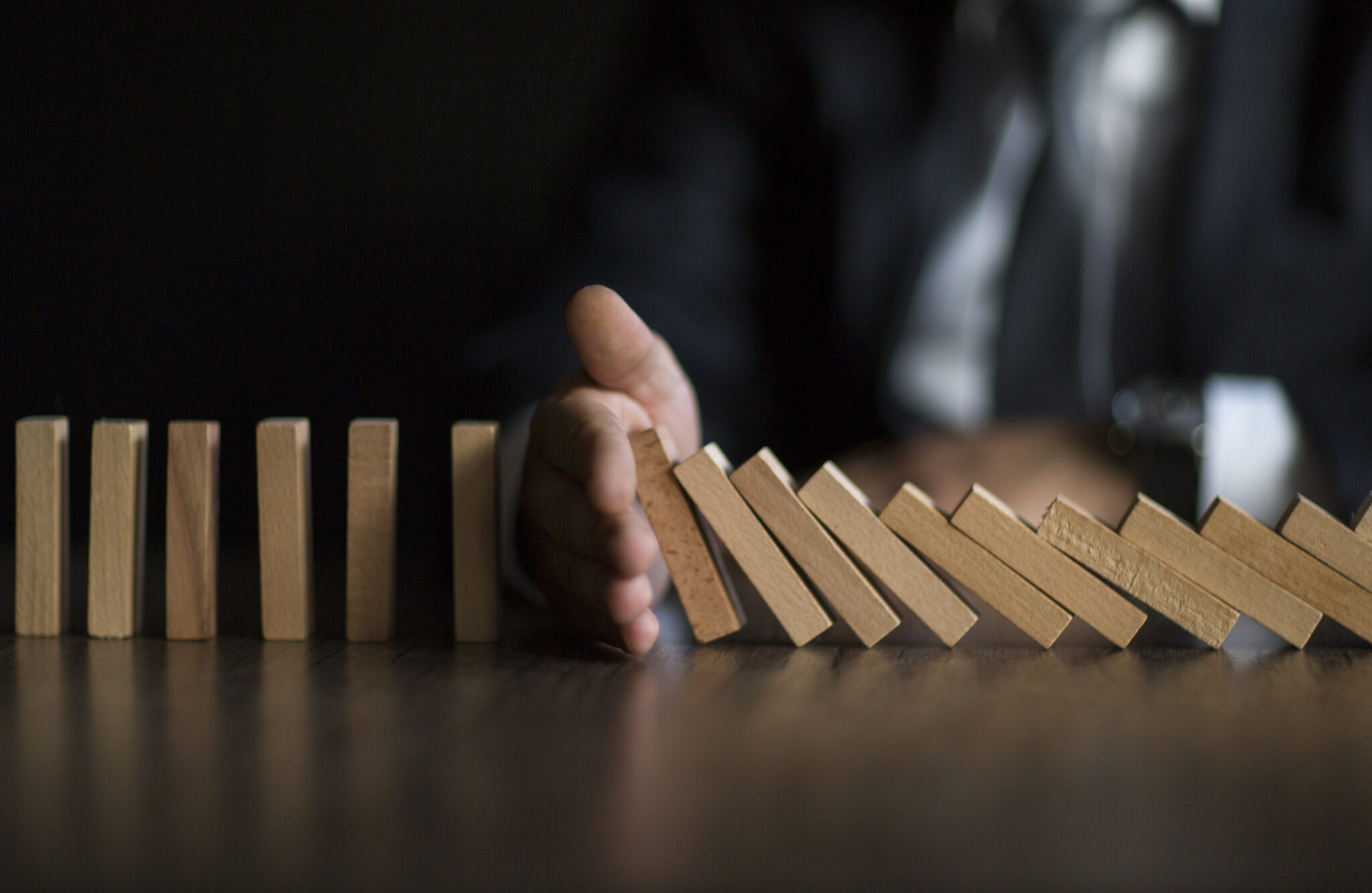 Businessman Stop Domino Effect. Risk Management and Insurance Concept - Canadian Underwriter