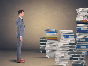 Businessman with stack of office files