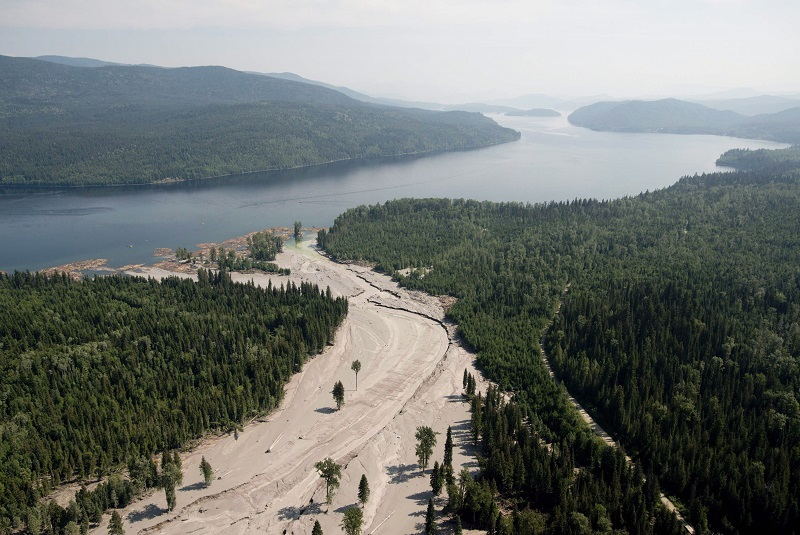 Tailings pond dam breaks spilling content into river