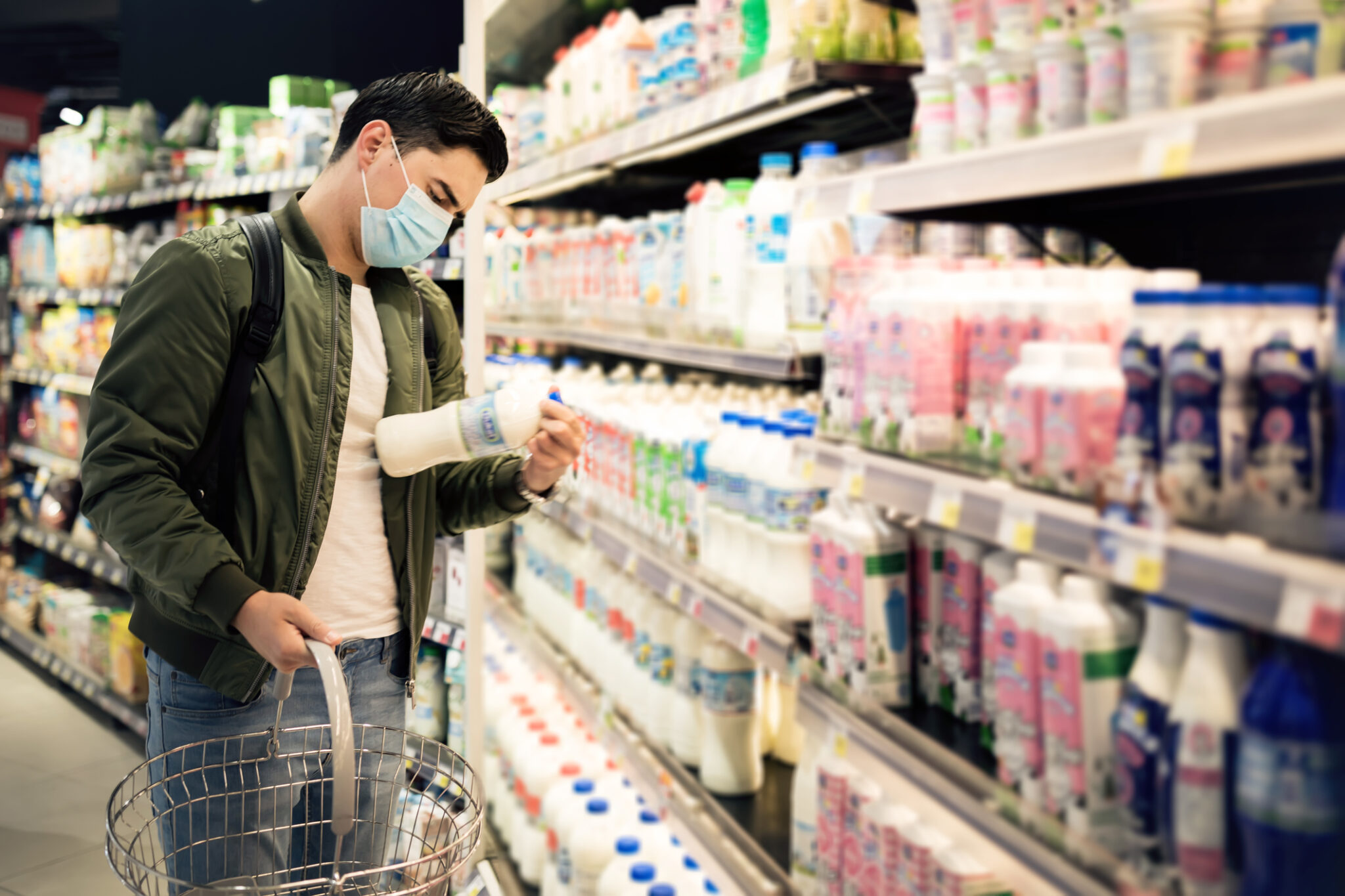Man shopping in a supermarket, breathing through a medical mask