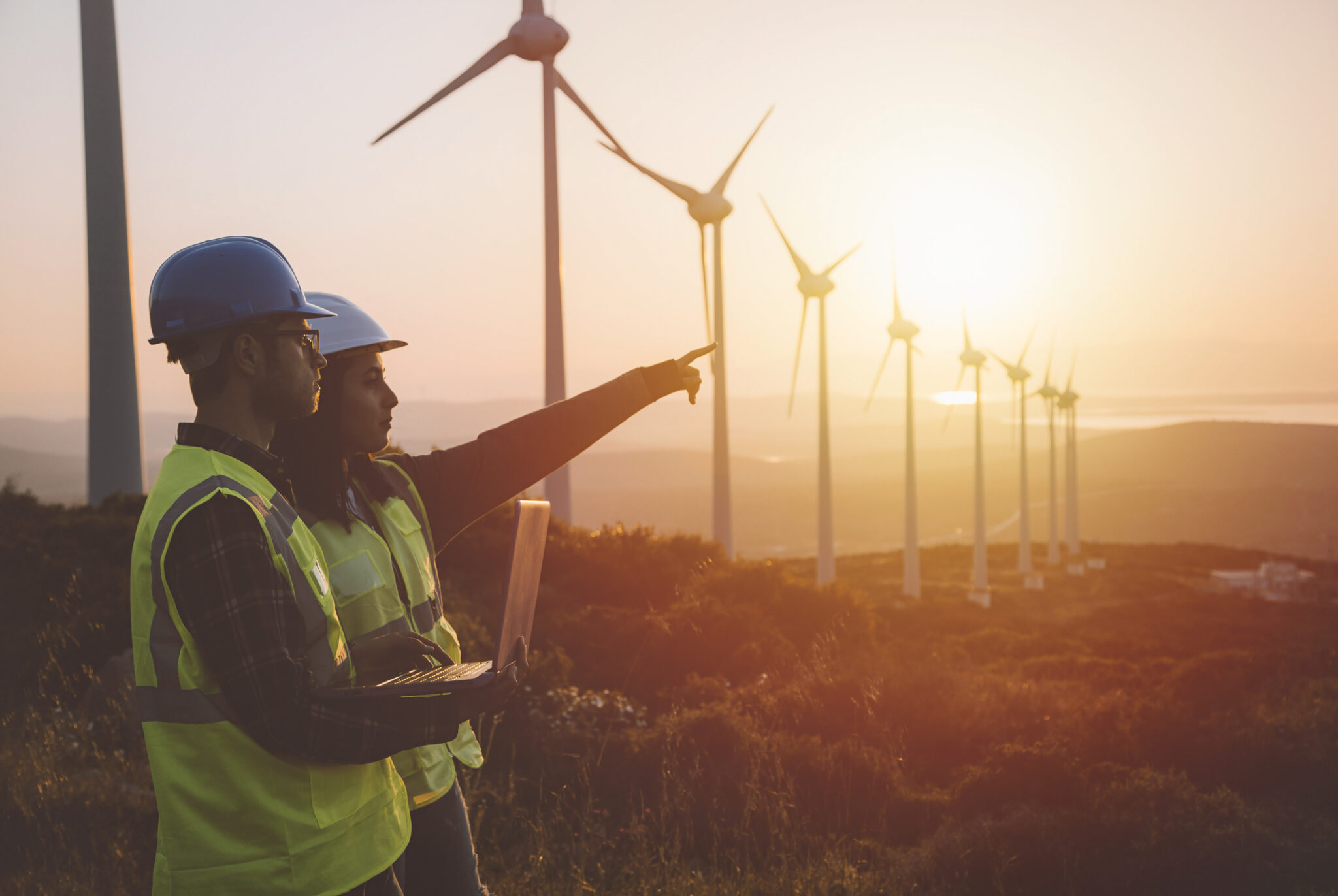 Young electrical engineer woman and business man standing in front of wind turbines checking and working about technical problems
