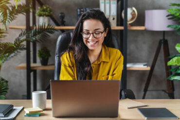 Young happy business woman sit indoors in home office using laptop computer
