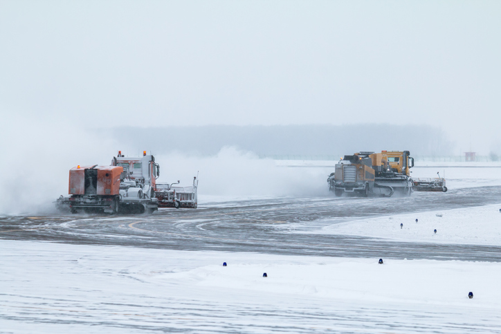 Snowblowers clearing snow off airport runway