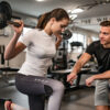 Fitness Instructor Guiding Young Woman When She Exercises stock photo
